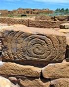 Spirale sculptée dans un bloc de grès au premier plan avec de grandes pièces en maçonnerie en pierre à l'arrière-plan.