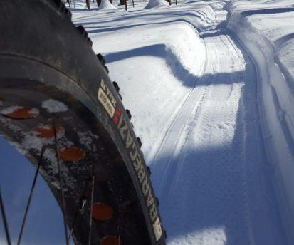 Fat bike pneu en premier plan avec piste de fat bike damée en arrière-plan