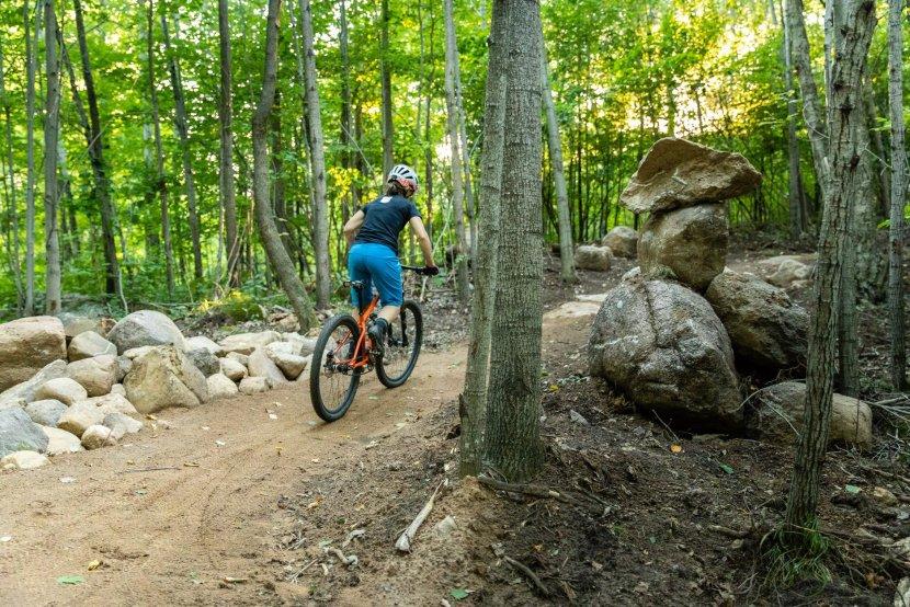 Woman riding a mountain bike loin de la caméra dans les bois