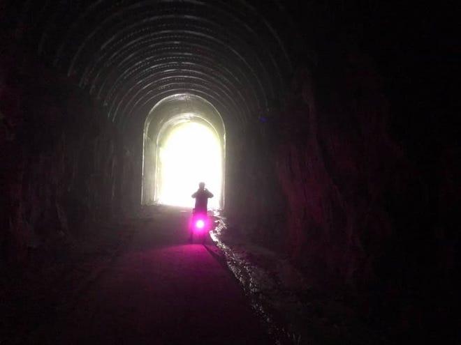 Faire du vélo dans un tunnel sur le sentier Omaha près de Camp Douglas.