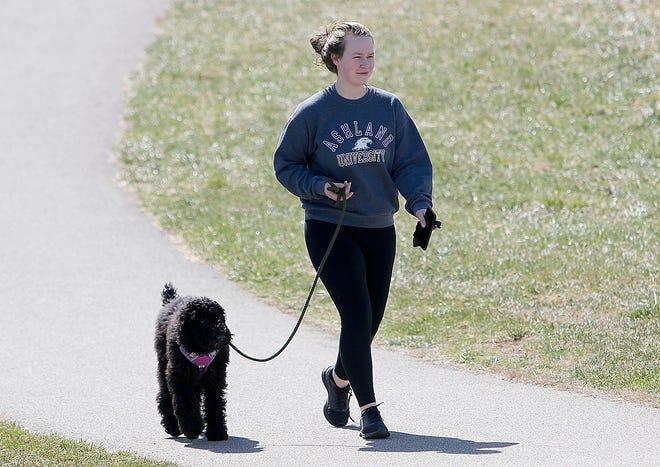 Carrie Hickey promène son chien lundi sur le sentier pavé de Freer Field.  Un temps plus clément permet à plus de gens de profiter du plein air.