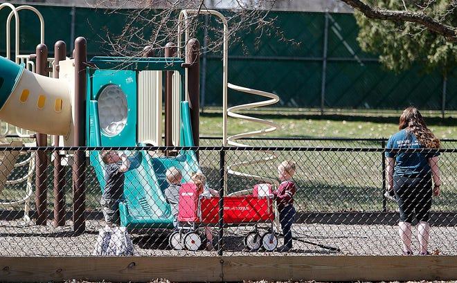 Les gens apprécient le beau temps lundi au Brookside Park Tot Lot.