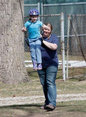 Heather Burden donne à sa fille, Grace, une poussée sur la balançoire lors de sa visite à Brookside Park lundi.