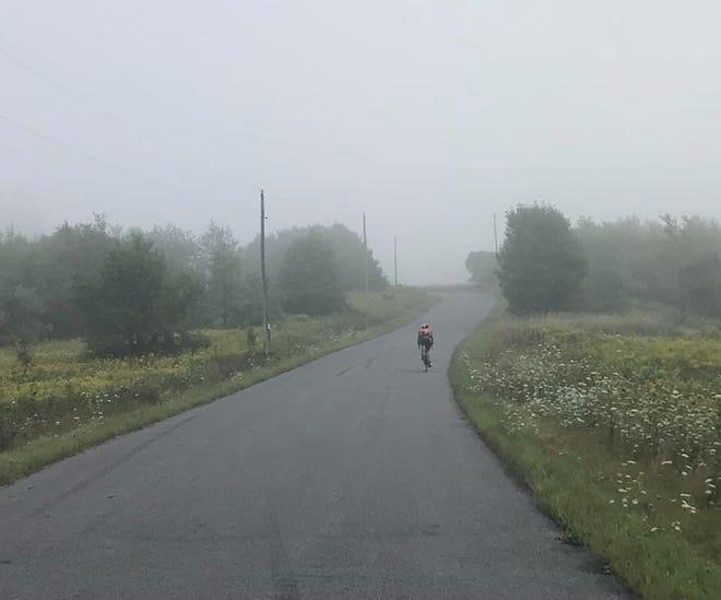 Un cycliste monte une colline dans le brouillard tôt le matin, au nord de Wausau.
