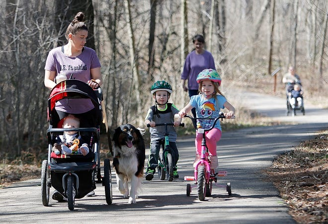 Tiffany Arnold profite d'une promenade lundi sur le sentier pavé avec ses enfants Boone (en poussette), Lane et Ella ainsi que leur chien, Bo, à Freer Field.
