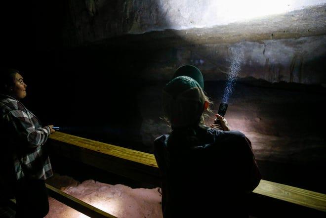 Hannah Davis, à droite, un ranger interprète saisonnier, illumine des parties de l'intérieur de la grotte pour Alaina Wichterman, à gauche, au Dunbar Cave State Park à Clarksville, Tennessee, le jeudi 20 mai 2021.