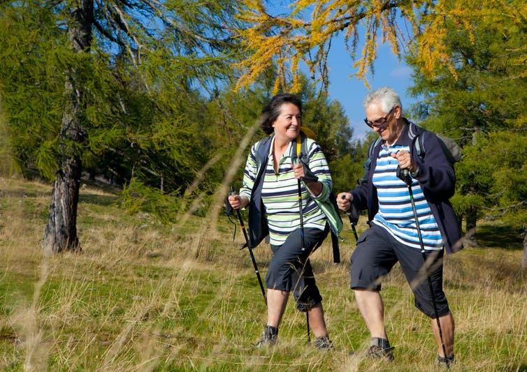 Un couple plus âgé utilise des bâtons de marche lors d'une randonnée.